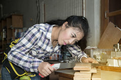 Pretty Asian woman using a hand saw to cut some wood. Royalty Free Stock Image