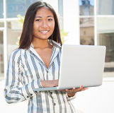 Pretty asian woman using a laptop Royalty Free Stock Image