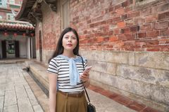 Pretty asian woman using the mobile for searching. She finds her destination stock photo