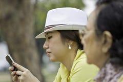 Pretty asian woman using a smart phone. Pretty asian women using a smart phone beside old woman Stock Photo