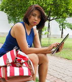 Pretty Asian woman using tablet at the park stock photography
