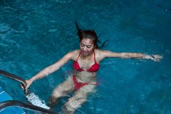 Pretty Asian woman wearing red bikini swim and standing at stair at swimming pool. stock photo