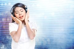 Pretty asian woman in white shirt listening music with headphones stock photography
