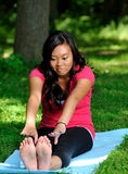 Pretty Asian woman - yoga in the park Royalty Free Stock Photos