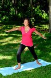Pretty Asian woman - yoga in the park Stock Image
