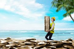 Pretty asian workers bringing coin stacks. Summer saving concept Stock Images