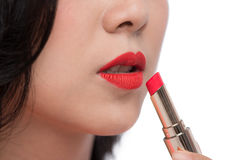 Pretty asian young woman applying red matt lipstick on her lips Royalty Free Stock Image
