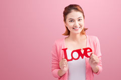 Pretty asian young woman holding wooden letters LOVE on link bac Stock Images