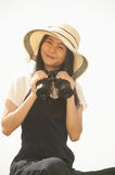 Pretty Asian young woman seeking Binoculars . Pretty Asian young woman in yellow hat seeking Binoculars Royalty Free Stock Images