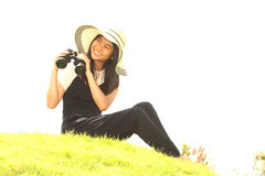 Pretty Asian young woman sit on mound seeking binoculars . Royalty Free Stock Photos