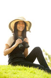 Pretty Asian young woman sit on mound seeking binoculars . Stock Images