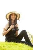 Pretty Asian young woman sit on mound seeking binoculars . Stock Images