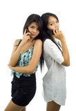 Pretty asians with mobile phones. Beautiful, young asian women talking on their mobile phone, isolated on white stock images