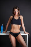 Pretty athlet posing with a sport drink. Beautiful happy fitness model posing with an isotonic sport drink Stock Photos