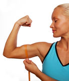 Pretty athlete measures biceps. Of her arms royalty free stock image