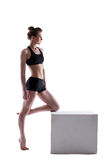 Pretty athletic brunette posing on cube Royalty Free Stock Image