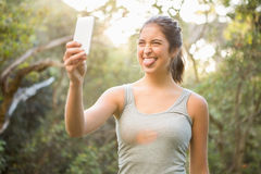 Pretty atlethic brunette taking selfie with outstretched tongue Stock Photos