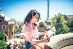 Pretty attractive girl studying map while traveling on a sunny day Stock Image