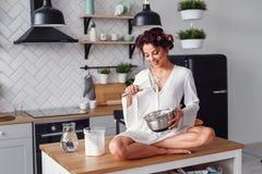 Attractive girl in white bathrobe having fun while preparing dough at stylish modern kitchen. Young pretty woman baking stock photo