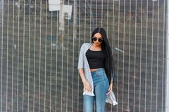 Pretty attractive hipster young woman in sunglasses in a vintage cape in a trendy top in stylish blue jeans is resting stock images