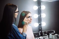 Pretty attractive makeup artist combing the eyebrows Stock Photo