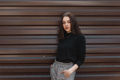 Pretty attractive young woman in a black elegant classic sweater in checkered vintage pants posing standing. Near a modern metal wall on a warm spring day stock photography