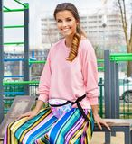Pretty attractive and young woman posing on the street in colourful clothes royalty free stock photos