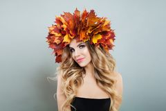 Pretty autumn woman portrait. Beautiful female model in bright fall leaves, makeup and curly haircut.  royalty free stock image