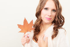 Pretty autumnal girl with maple leaf in hand Stock Image