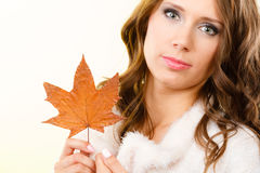 Pretty autumnal girl with maple leaf in hand Stock Photography
