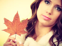 Pretty autumnal girl with maple leaf in hand Stock Photo
