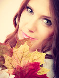 Pretty autumnal girl with maple leaves in hand Royalty Free Stock Images