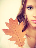 Pretty autumnal girl with oak leaf in hand Stock Photography