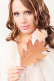Pretty autumnal girl with oak leaf in hand Royalty Free Stock Image