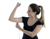 Pretty babe measuring her biceps. Beautiful young woman measuring her biceps with a tape Royalty Free Stock Images