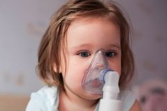 Adorable little girl receives breathing treatment stock image