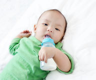 Pretty baby boy drinking milk from bottle Royalty Free Stock Images