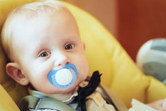 Pretty Baby Boy Sitting In Yellow Seat With Soother Stock Photos