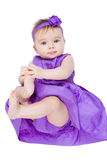 Pretty Baby Girl. Pretty young baby girl in her purple dress and headband looking at camera Royalty Free Stock Images