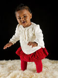 Pretty baby girl. A beautiful multi racial nine month old baby girl standing on a deep white fur against a black background wearing a white sweater and red skirt Stock Images