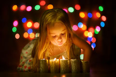 Pretty baby girl blowing out the candles and makes a wish. Night shot of the baby girl with candles with beautiful bokeh at background Stock Photo
