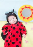 Pretty baby girl, dressed in ladybug costume on green background. Stock Images
