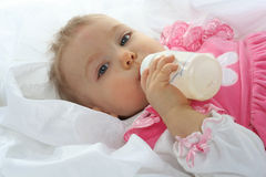 Pretty baby girl is drinking milk Royalty Free Stock Images