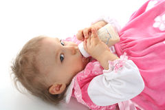 Pretty baby girl is drinking milk Stock Images