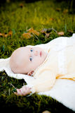 Pretty baby girl on grass. Small serious baby girl lying on the grass in autumn and looking at camera stock images