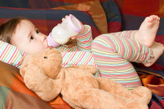 Pretty baby girl with infant formula in bottle Stock Photography