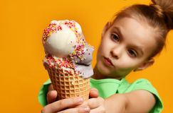 Pretty baby girl kid eating licking banana and strawberry ice cream in waffles cone. On yellow background with free text copy space Stock Images