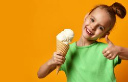 Pretty baby girl kid eating licking vanilla ice cream in waffles cone. On yellow background stock images