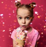 Pretty baby girl kid holding ice cream in waffles cone with raspberry showing surprised. On red background Stock Photos