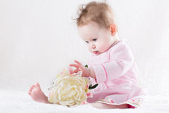 Pretty baby girl playing with a big white flower. Pretty little baby girl playing with a big white flower Stock Photo
